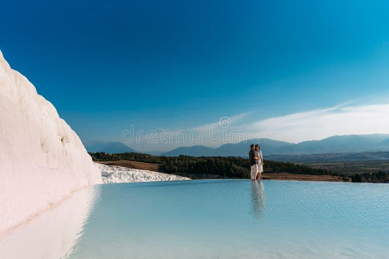 Para w miłość uściśnięciach blisko pięknego błękitnego jeziora fotografia stock