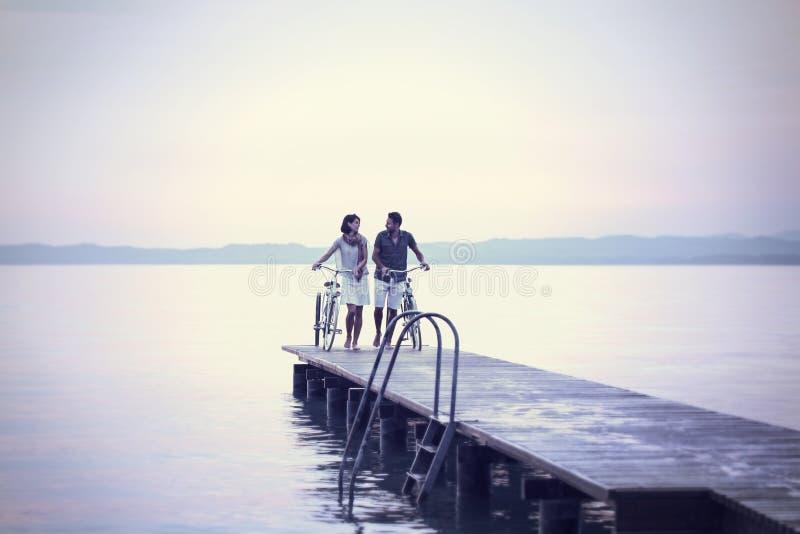 Para w miłości pcha rower na boardwalk przy jeziorem obrazy stock