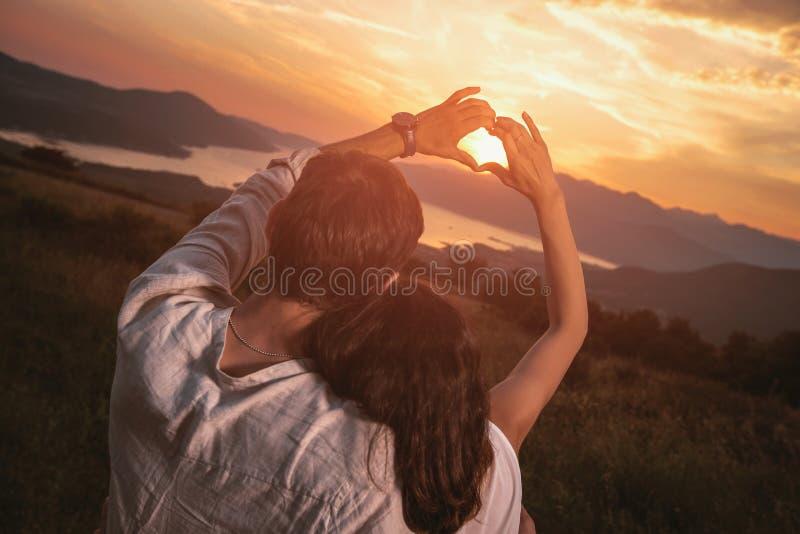 Para w miłości robi sercu - kształtuje z rękami, patrzeje zmierzch obrazy royalty free