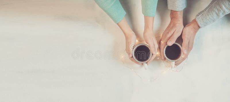 Para w miłości trzyma ręki z kawą na bielu marmuru stole z bożonarodzeniowymi światłami, Fotografia brać od above, wierzchołek obraz stock
