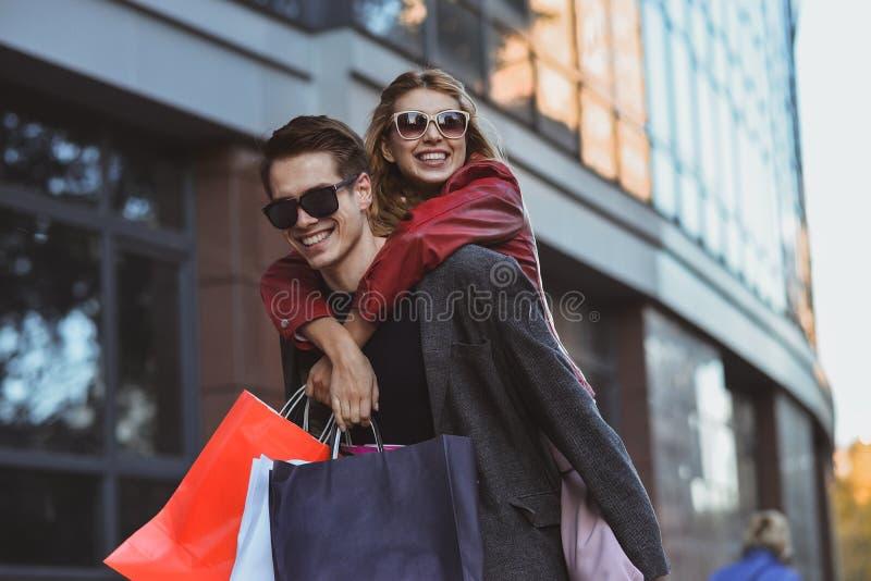 Para w robić zakupy wpólnie Szczęśliwa para robi zakupy wpólnie i ma zabawę Chłopak niesie jego dziewczyny na piggyback fotografia royalty free