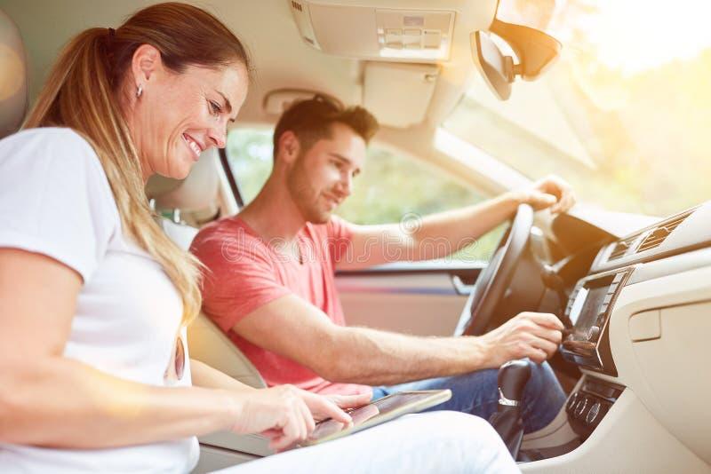Para w samochodzie używa GPS jako Navi na pastylce fotografia stock
