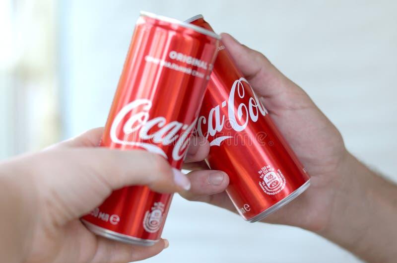 Para wręcza podwyżkom czerwone koka-kola puszki w garażu wnętrzu obraz stock