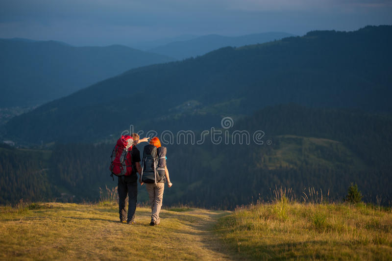 Para wycieczkowicze trzyma ręki z plecakami, chodzi w górach obraz stock