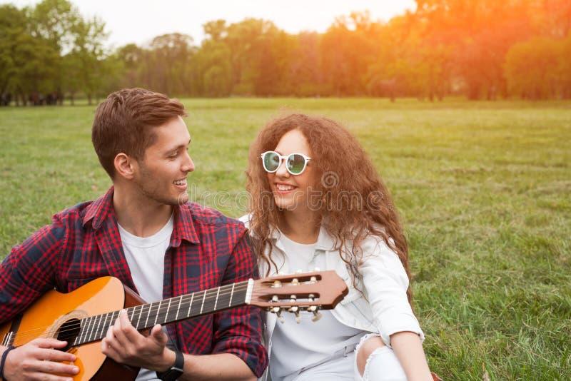 Para wydaje czas w parku z gitarą obraz stock