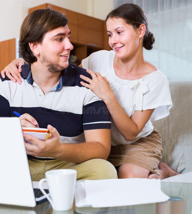 Para wyszukuje sieć i robi notatkom indoors fotografia royalty free