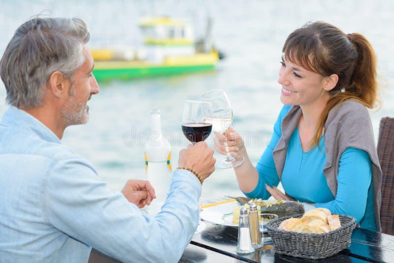 Para wznosi toast przy nadrzeczną restauracją zdjęcia royalty free