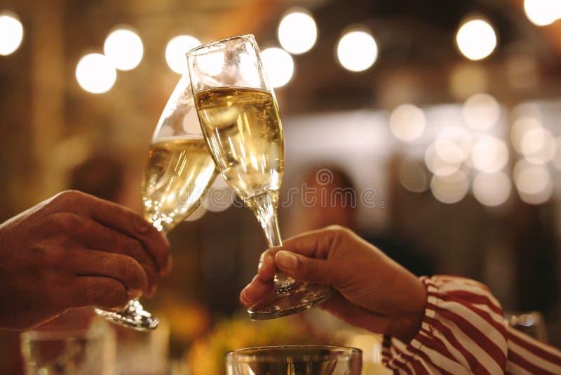 Para wznosi toast szampańskich szkła przy przyjęciem zdjęcia stock