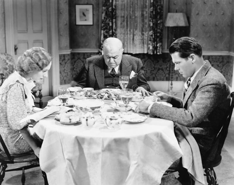 Para z ich ojca obsiadaniem przy łomota stołem i ono modli się (Wszystkie persons przedstawiający no są długiego utrzymania i żad fotografia stock