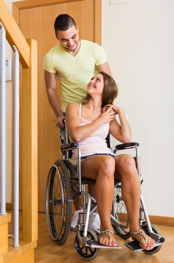 Para z kobietą w wózku inwalidzkim blisko drzwi zdjęcia royalty free