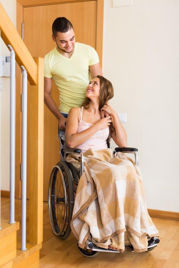 Para z kobietą w wózku inwalidzkim blisko drzwi obrazy stock