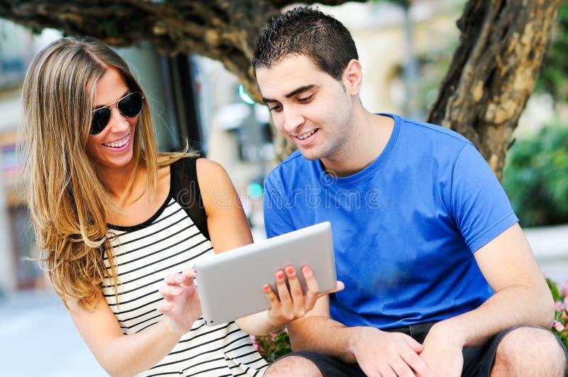Para z pastylki komputerem w miastowym tle obraz royalty free