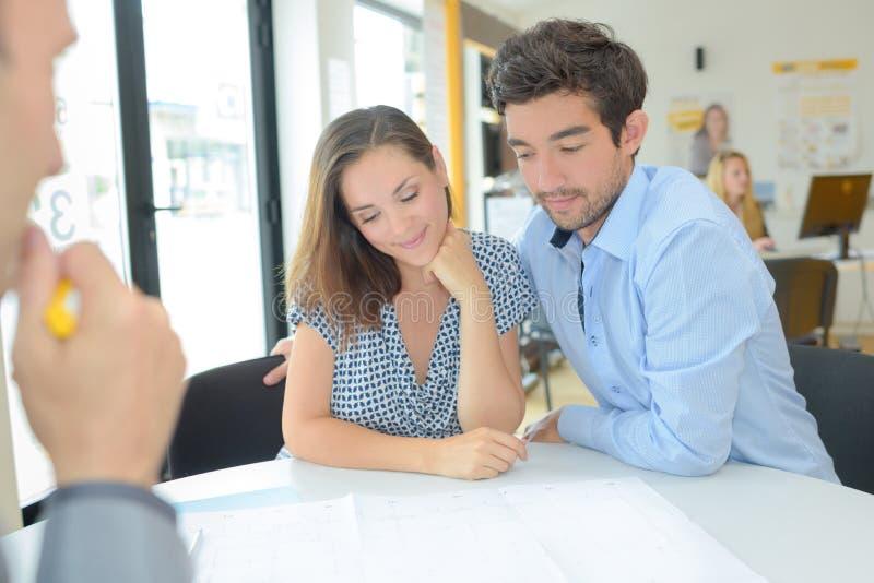 Para z pośrednik w handlu nieruchomościami patrzeje projekty zdjęcia royalty free