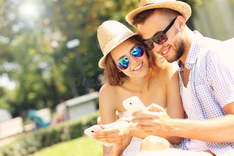 Para z smartphones w parku zdjęcie royalty free
