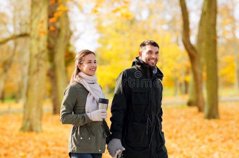 Para z tumbler odprowadzeniem wzdłuż jesień parka fotografia royalty free