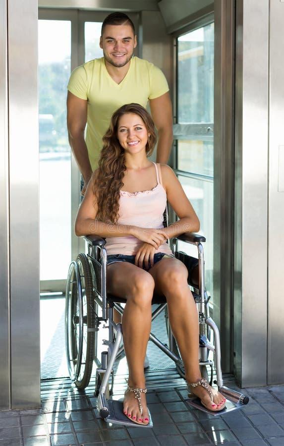 Para z wózkiem inwalidzkim w windzie fotografia stock