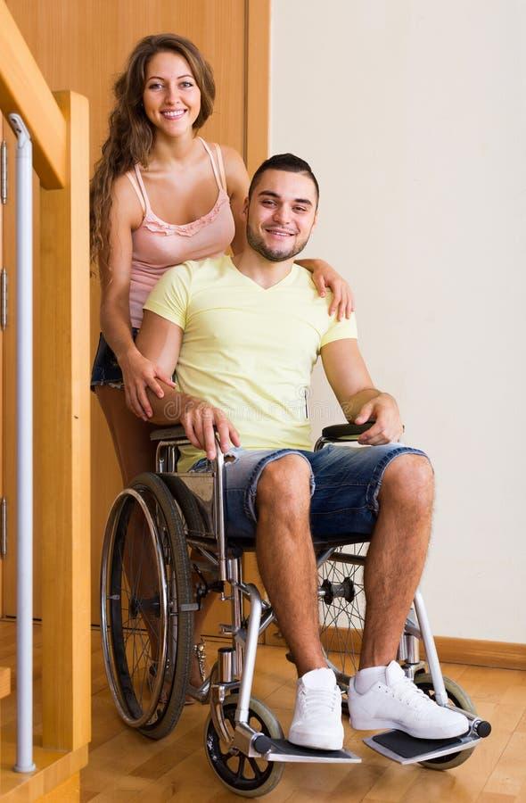 Para z współmałżonkiem w wózku inwalidzkim blisko drzwi zdjęcia royalty free