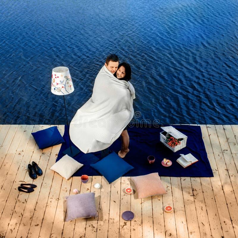 Para zakrywająca powszechną pozycją na tarasie blisko wody obrazy stock