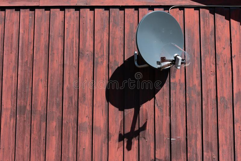 Parabolic antenna on an old wooden wall stock images