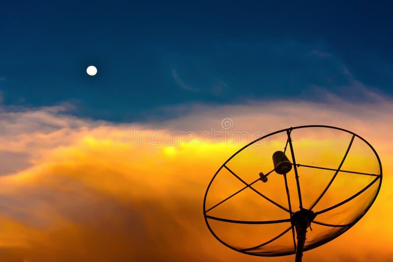 Parabolische Satellitenschüssel in der Dämmerung mit Mond stockfotografie