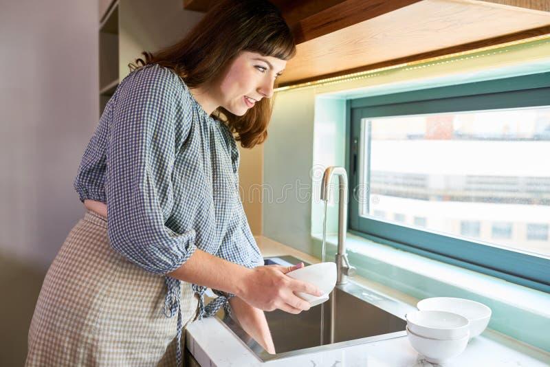 Paraboloïdes de séchage de femme dans la cuisine image libre de droits