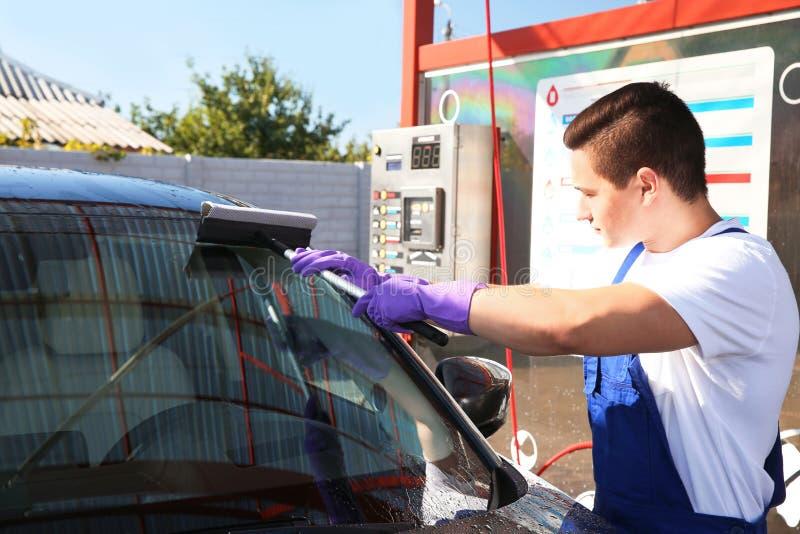 Parabrisas de limpieza del automóvil del trabajador imágenes de archivo libres de regalías