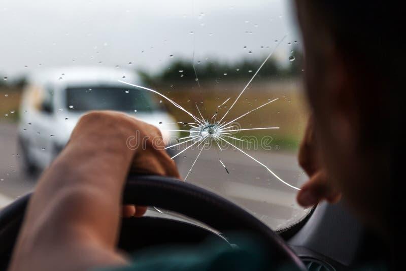 Parabrisas quebrado de un coche Una web de fracturas radiales, grietas en el parabrisas triple Parabrisas quebrado del coche, vid imagen de archivo libre de regalías
