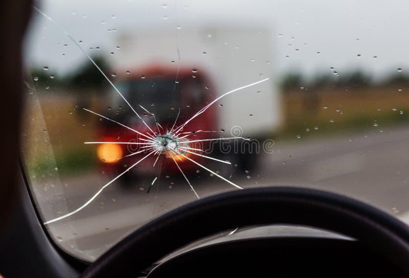 Parabrisas quebrado de un coche Una web de fracturas radiales, grietas en el parabrisas triple Parabrisas quebrado del coche, vid fotos de archivo libres de regalías