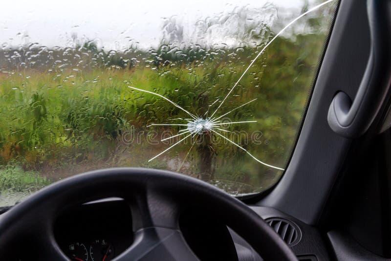 Parabrisas quebrado de un coche Una web de fracturas radiales, grietas en el parabrisas triple Parabrisas quebrado del coche, vid foto de archivo