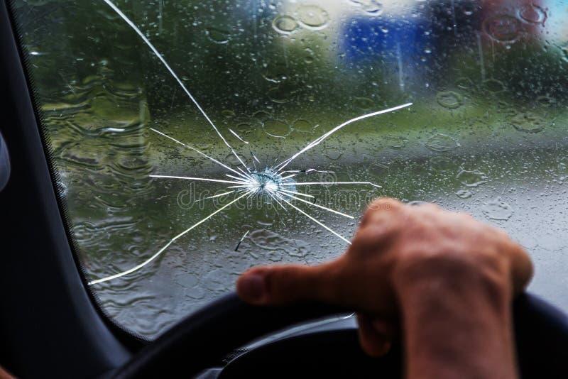 Parabrisas quebrado de un coche Una web de fracturas radiales, grietas en el parabrisas triple Parabrisas quebrado del coche, vid imagen de archivo