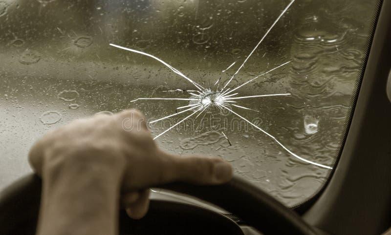 Parabrisas quebrado de un coche Una web de fracturas radiales, grietas en el parabrisas triple Parabrisas quebrado del coche, vid fotos de archivo