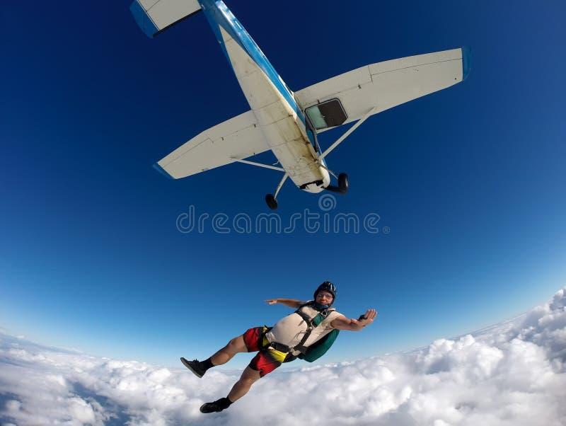 Paracadutista in abbigliamento casual che salta giù l'aereo un giorno di estate immagine stock