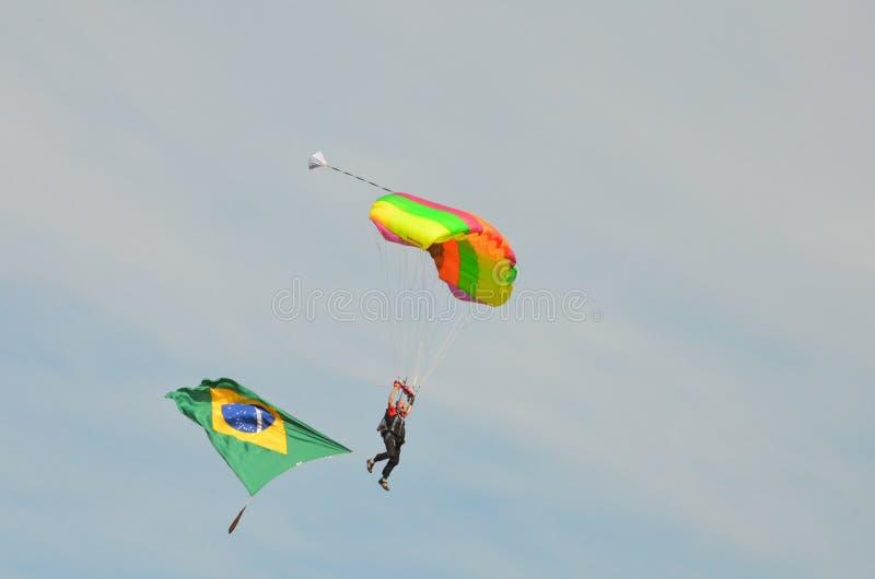 Paracadutista che va atterrare tenuta della bandiera brasiliana durante il volo immagini stock