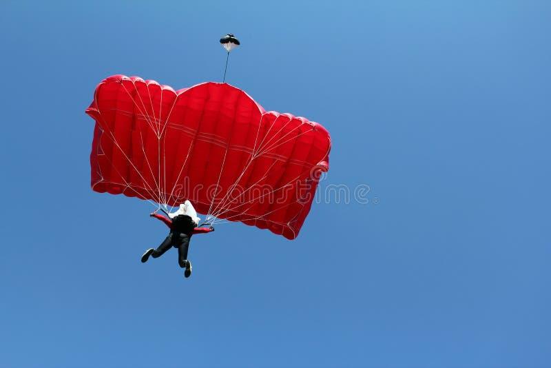 Paracaidista con el paracaídas rojo fotografía de archivo