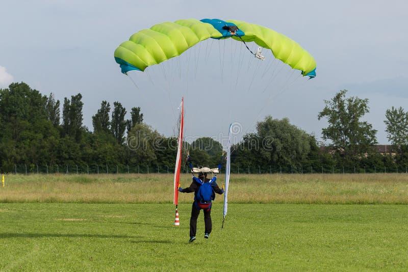 Paracaidista con el paracaídas verde cerca a la tierra que se prepara para aterrizar imagenes de archivo