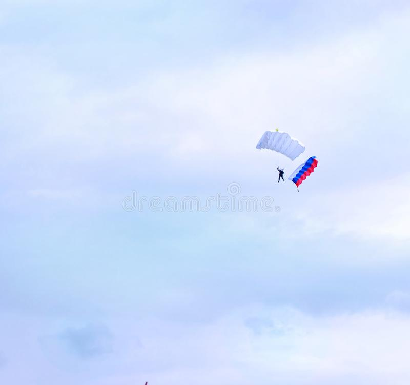 Paracaidista con la bandera rusa en cielo imagen de archivo