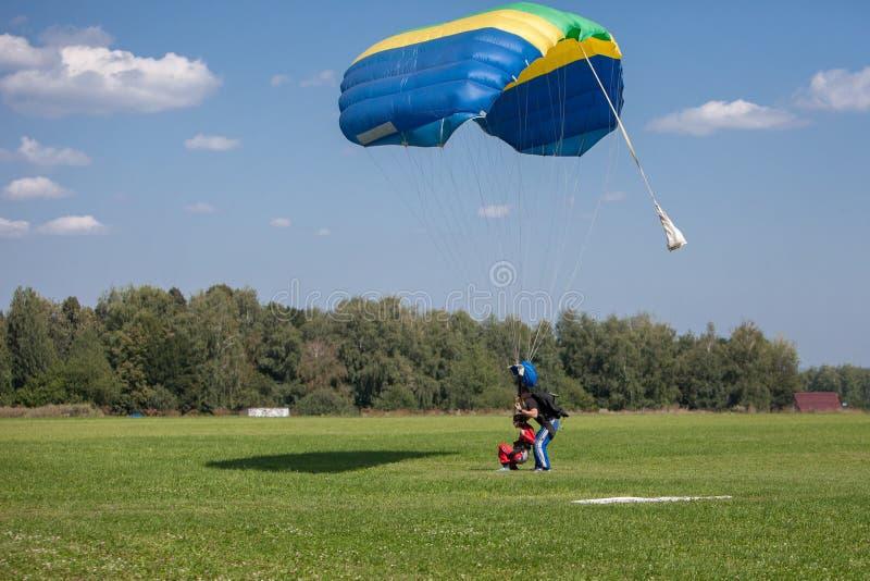 Paracaidista de los Skydivers en el cielo azul en puesta del sol imágenes de archivo libres de regalías