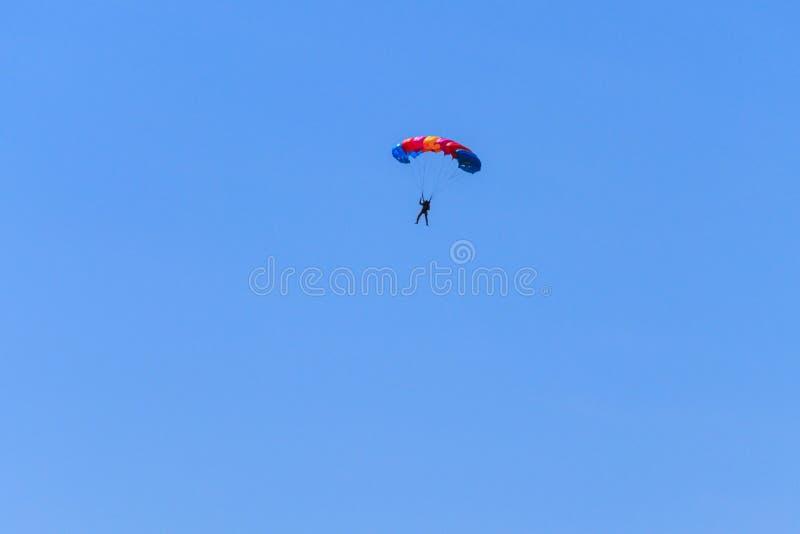 Paracaidista que desciende con el paracaídas contra el cielo azul imagenes de archivo