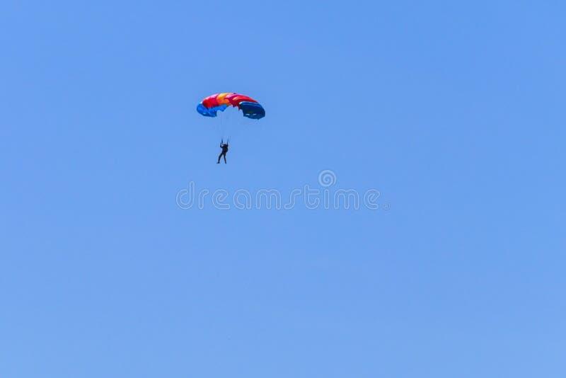Paracaidista que desciende con un paracaídas contra el cielo azul imágenes de archivo libres de regalías