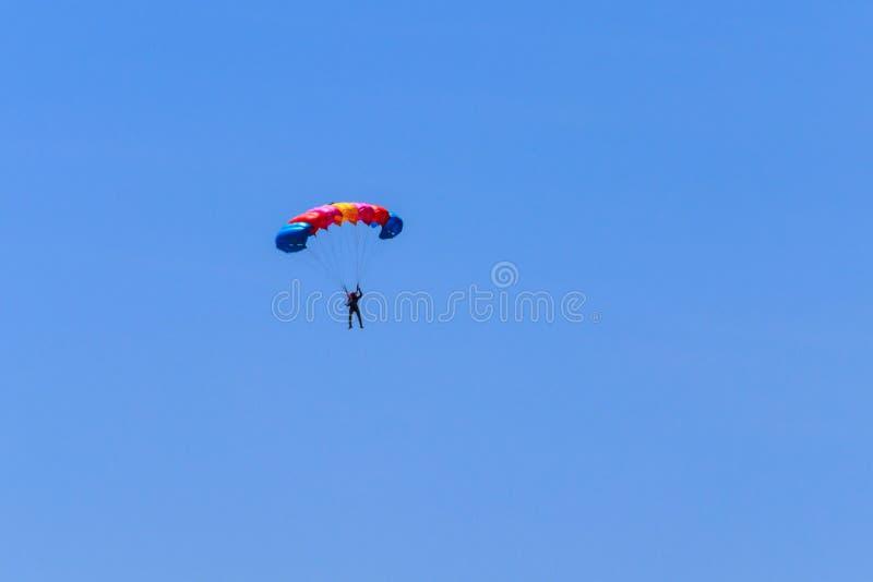 Paracaidista que desciende con un paracaídas contra el cielo azul fotos de archivo