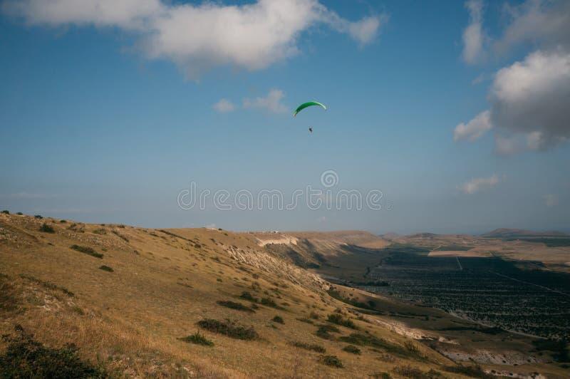 Paracaidista que se desliza en cielo azul sobre el paisaje escénico de Crimea, Ucrania, fotografía de archivo libre de regalías