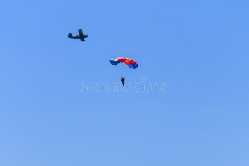 Paracaidista y aeroplano en cielo azul Forma de vida activa Deporte extremo imagen de archivo
