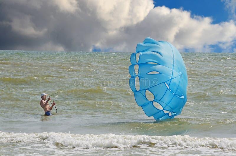 parachutage L'homme en mer bleue maintient le parachute dans le vent image libre de droits