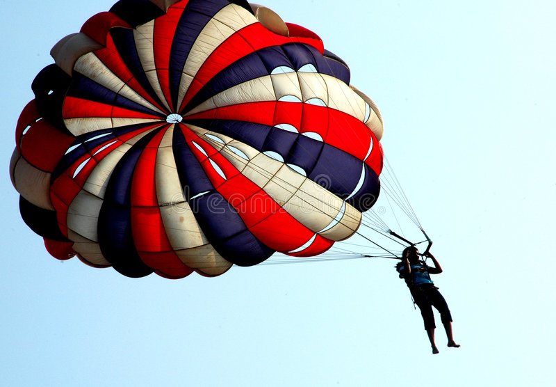 Parachute. Person trying to land with the help of beautifully coloured parachute stock photo