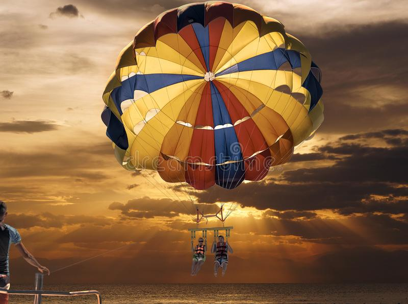 Parachute ascensionnel heureux de couples sur la plage tropicale en été Couples sous le plein vol accrochant de parachute Avoir l photo stock