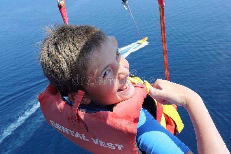 Parachute ascensionnel heureux de garçon haut au-dessus de la mer image stock