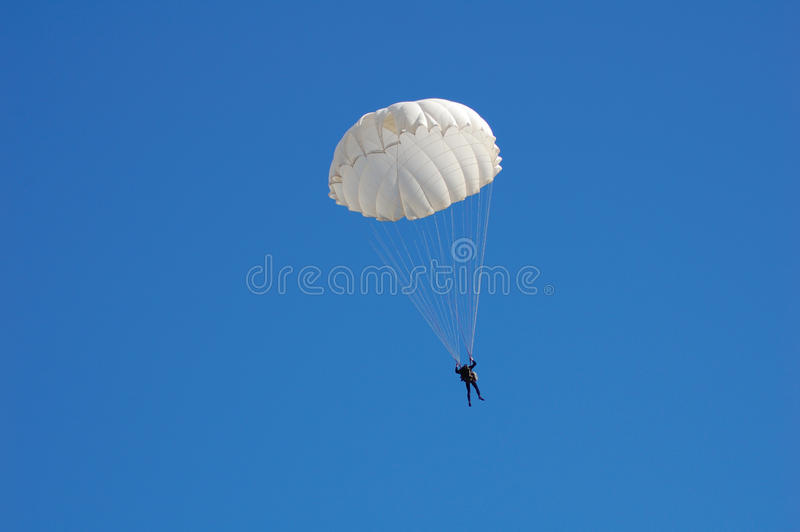 Parachute jumper. In blue sky royalty free stock photo