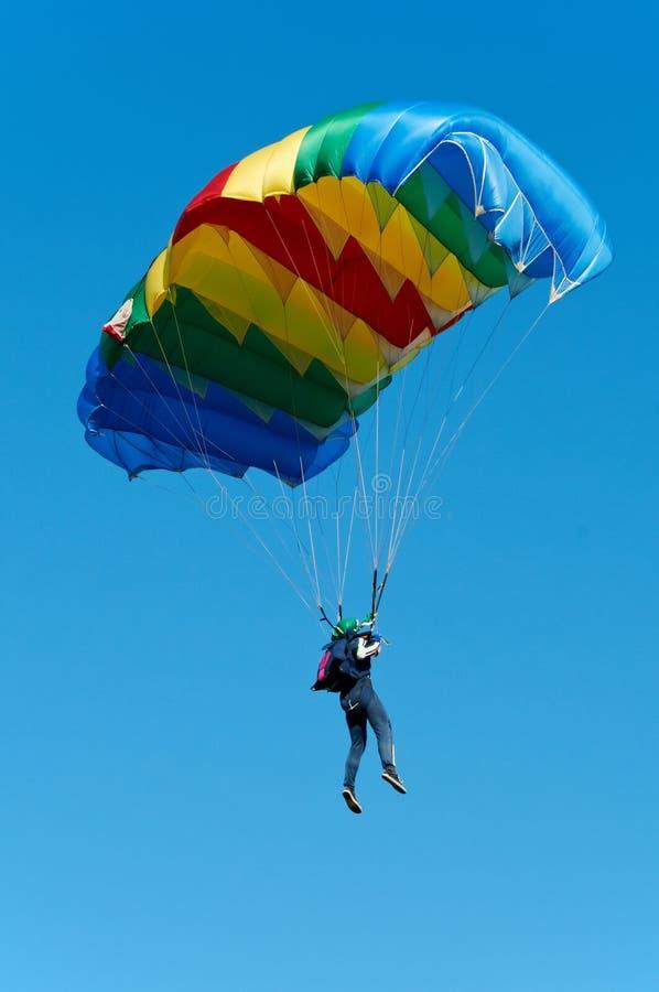 Parachute jumper. Single parachute jumper against blue sky background stock photo