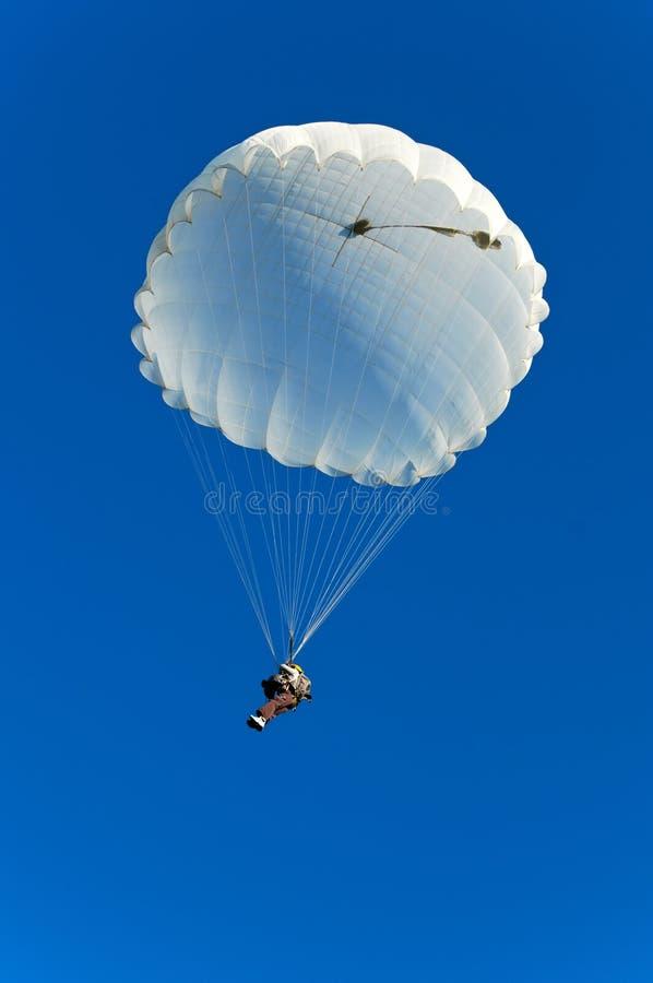 Parachute jumper. Single parachute jumper against blue sky background stock photography
