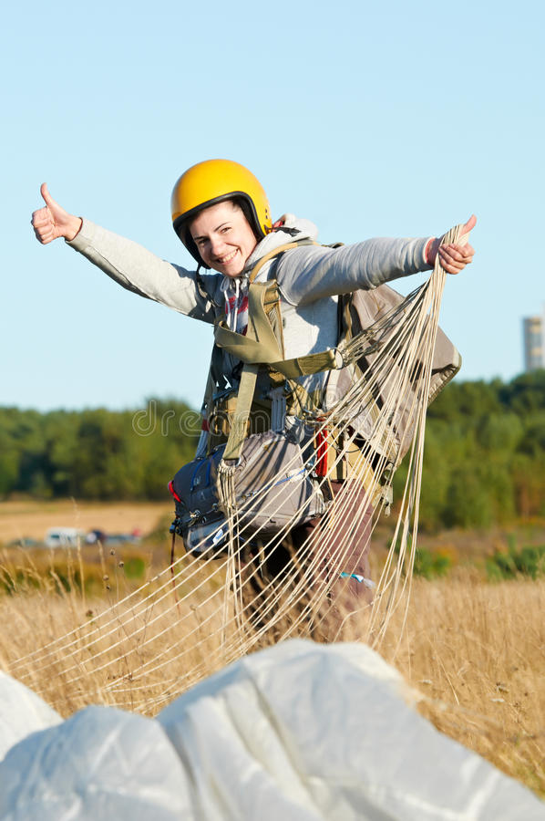 Parachute jumper after landing. Single Happy parachute jumper after landing at field and blue sky background stock image
